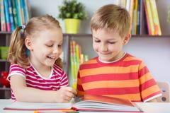 Zwei glückliche Geschwister, die interessantes Buch lesen Lizenzfreies Stockbild