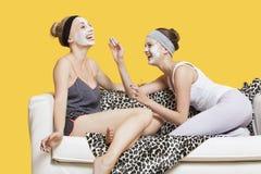 Zwei glückliche junge Frauen, die Gesichtsmaske beim Sitzen auf Sofa über gelbem Hintergrund anwenden Stockfotografie