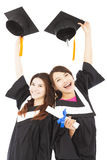 Zwei glückliche junge Studenten im Aufbaustudium, die Hüte und Diplom halten Stockfotografie