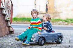 Zwei glückliche Kinder, die mit großem altem Spielzeugauto im Sommer spielen, arbeiten, ou im Garten Lizenzfreies Stockbild