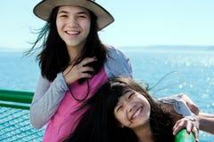 Zwei glückliche Mädchen, die auf Fährenplattform mit Ozean im Hintergrund lächeln Stockbilder