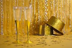 Zwei Goldchampagne-Flöten mit Sequined Party-Hüten Stockbilder