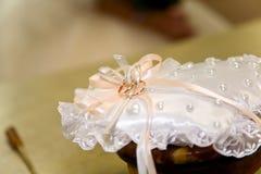 Zwei Goldeheringe auf einem weißen Kissen verzierten mit den Perlen Stockbilder