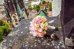 Zwei Goldeheringe in einer schönen Form in Form eines Herzens und eines Blumenstraußes von rosa Blumen am Rand des Fensterbretts Lizenzfreie Stockbilder
