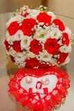 Zwei Goldeheringe liegen auf einem Kissen in Form eines Herzens mit einem roten Spitzeblumenstrauß von roten und weißen Rosen Lizenzfreies Stockbild