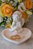 Zwei Goldeheringe liegen auf einer Servierplatte in einer Rosenform mit der Engelsskulptur nahe dem bride& x27; s-Blumenstrauß Stockfoto