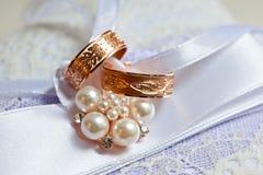 Zwei Goldeheringe mit Mustern auf einem schönen Kissen mit Dekorationen Stockbild