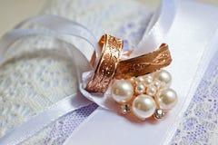 Zwei Goldeheringe mit Mustern auf einem schönen Kissen mit Dekorationen Lizenzfreies Stockfoto