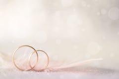 Zwei goldene Eheringe und Feder - heller weicher Hintergrund Stockbilder