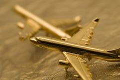 Zwei goldene Flugzeuge auf Goldfolie Stockbild