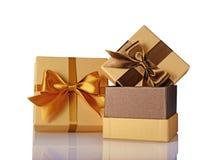Zwei goldene klassische glänzende Geschenkboxen mit braunem Satin beugt Stockfoto