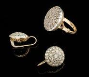 Zwei goldene Ohrringe und Ring mit Diamanten Stockfotos