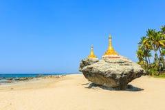Zwei goldene Pagoden auf Felsen auf Ngwesaung setzen, Westküste von Myanmar auf den Strand Lizenzfreie Stockbilder