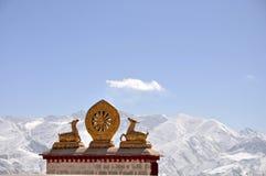 Zwei goldene Rotwild, die ein Dharma-Rad und einen Schneeberg angrenzen Stockfotografie