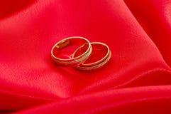 Zwei Goldhochzeitsringe auf dem Rot Lizenzfreie Stockfotografie