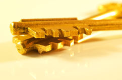 Zwei Goldschlüssel auf einem hellen Hintergrund Stockfotos