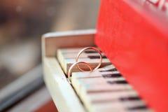 Zwei golgen Ringe auf Klavier Stockfotos