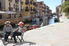 Zwei Gondel-Mann-Leute, die in Venedig-Canal Street sprechen stockfotografie