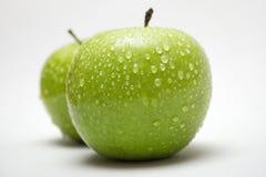 Zwei grüne Äpfel mit Regentropfen (Seitenansicht) Lizenzfreie Stockfotos