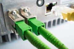 Zwei grüne optische Verbindungskabel eingefügt in die grünen optischen Häfen stockfotos