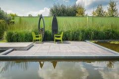 Zwei grüne Stühle mit einem modernen Kamin im Freien Stockfotos