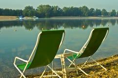 Zwei grüne Stühle am Strand von Ada See in Belgrad Stockbild