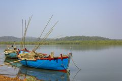 Zwei große alte Fischerboote mit den Motoren und Angeln verankert vor der Küste gegen den Hintergrund von einem Fluss und von grü stockfotos
