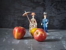 Zwei große rote Äpfel und Figürchen der Gorodets-Malerei im Hintergrund gegen einen grauen beschmutzten Hintergrund lizenzfreies stockfoto