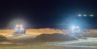 Zwei Grundarbeitskräfte, die nachts in den Planierraupen am Strand bewegt den Sand arbeiten lizenzfreie stockfotos