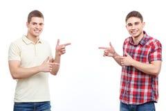 Zwei gutaussehende Männer, die auf lokalisiertem Hintergrund aufwerfen Stockfotografie