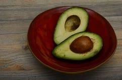 Zwei Hälften der Avocado auf roter keramischer Schüssel Stockfotos