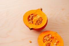 Zwei Hälften des rohen Kürbises mit Samen auf hölzernem Hintergrund lizenzfreie stockfotografie