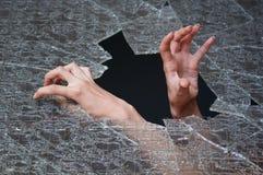 Zwei Hände bilden ihre Methode durch das unterbrochene Glas Stockfoto