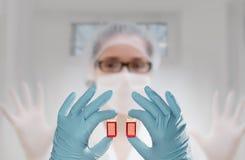 Zwei Hände in den Handschuhen halten zwei flüssige Proben vor einer Technologie Stockbilder
