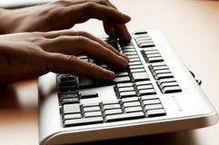 Zwei Hände, die an der Tastatur arbeiten Stockbild