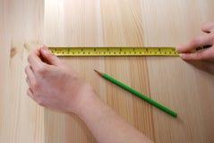 Zwei Hände messen ein hölzernes Brett mit einem StahlMaßband Stockfotografie