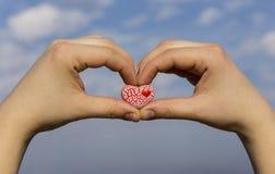 Zwei Hände, die ein rotes gesprenkeltes Herz gegen den blauen Himmel halten stockfotos