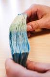 Zwei Hände, die einen Stapel von zehn Eurorechnungen halten Lizenzfreies Stockfoto