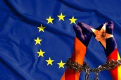 Zwei Hände die Flagge von Katalonien shackled eine Metallkette auf dem Hintergrund der EU-Flagge Lizenzfreies Stockfoto