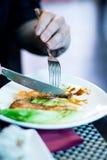 Zwei Hände, die gegrillte Lachsfische mit Salat auf einer weißen Platte mit Gabel und Messer schneiden Lizenzfreie Stockfotos