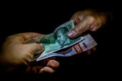 Zwei Hände, die miteinander Banknoten der norwegischen Kronen überreichen lizenzfreie stockfotografie