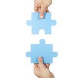 Zwei Hände, die Puzzlespielstücke anschließen Stockfotografie