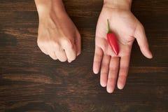 Zwei Hände, die roten Pfeffer anbieten stockfotos