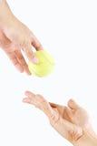 Zwei Hände, die Tennisball senden Stockfoto