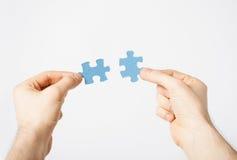 Zwei Hände, die versuchen, Puzzlespielstücke anzuschließen Lizenzfreie Stockbilder