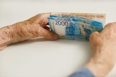 Zwei Hände eines Pensionärs halten Geld von einem großen Die Hände eines Mannes sind alt, altersschwach stockfotos