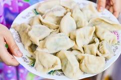 Zwei Hände halten eine Platte von gekochten chinesischen Mehlklößen Jiaozi Stockfoto