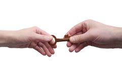 Zwei Hände, Mann und weiblicher Durchlauf der alte Schlüssel lokalisiert auf weißem Hintergrund Lizenzfreie Stockfotos
