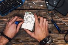 Zwei Hände mit Schraubenzieher bauen HDD auseinander lizenzfreie stockfotografie
