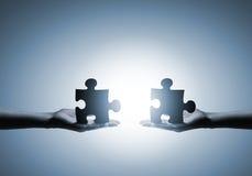 zwei Hände mit verschiedenen Stücken des Puzzlespiels Stockfotografie